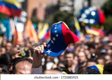 Caracas, Venezuela - 12 February 2019: A protester holds a cap with the Venezuelan flag during a demonstration against the government of Nicolás Maduro in Caracas, Venezuela.
