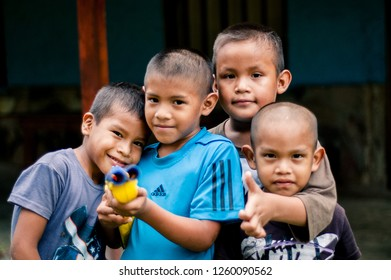 caracas, venezuela - 20 june 2018: group of childring playing and pointing toy gun toward camera. Venezuela is now the country with high homicides and violence rates in the world