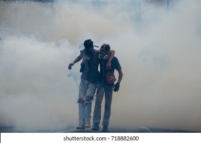 CARACAS, VENEZUELA - APRIL 19, 2017: Protest in Caracas, Venezuela. Two young Venezuelans of resistance in a cloud of tear gas fired by the national guard repressing the protest.