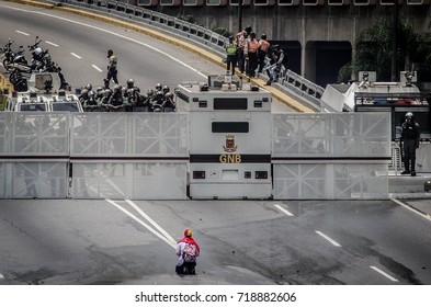 CARACAS, VENEZUELA - APRIL 19, 2017: Protest in Caracas, Venezuela. An old lady kneels in front of the national guard to ask them to stop the repression against the people.