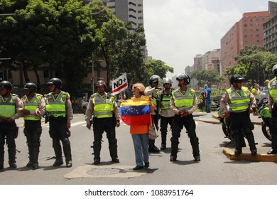 Caracas/ Venezuela - April 20, 2017: An elderly demonstrator defy riot police during a rally against Venezuela's President Nicolas Maduro. Venezuelans protest over food and medicine shortages