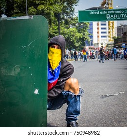 CARACAS, VENEZUELA - APRIL 26, 2017: Protest in Caracas, Venezuela against the government of Nicolas Maduro. A protester with a Venezuelan flag covering his face and a shield.