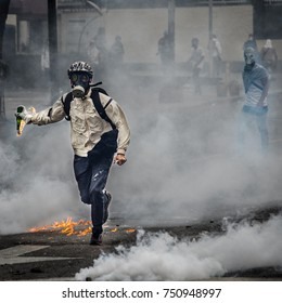 CARACAS, VENEZUELA - APRIL 26, 2017: Protest in Caracas, Venezuela against the government of Nicolas Maduro. Protester launches a molotov cocktail to the national guard.