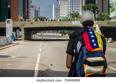 CARACAS, VENEZUELA - APRIL 26, 2017: Protest in Caracas, Venezuela against the government of Nicolas Maduro. A protester with the flag of Venezuela in front of the Bolivarian National Guard