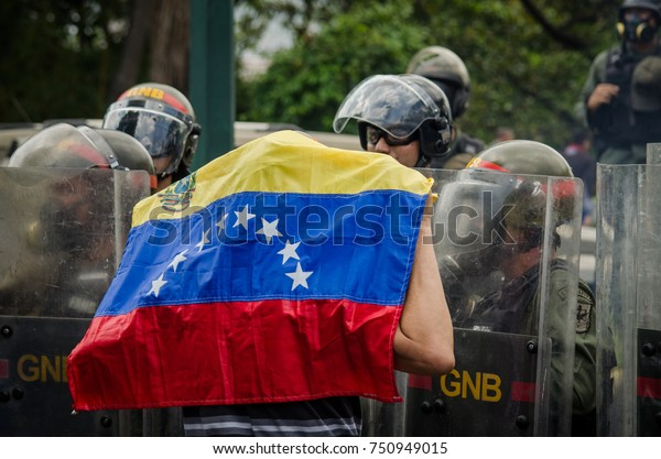 CARACAS, VENEZUELA - APRIL 26, 2017: Protest in Caracas, Venezuela against the government of Nicolas Maduro. Demonstrator with the venezuelan flag in front of the national guard.