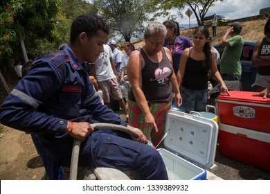 Caracas, Venezuela, March 12, 2019: A group of people try to collect water from Avila due to the shortage of liquid after the electric blackout in Venezuela.