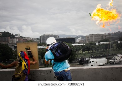 CARACAS, VENEZUELA - MAY 01, 2017: A member of the Venezuelan resistance launches a Molotov bomb to the tanks of the national guard