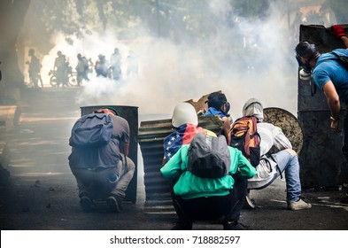CARACAS, VENEZUELA - MAY 01, 2017:  A group of young Venezuelan resistance protecting themselves with shields from the shots of the national guard suppressing the protest.