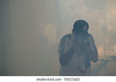 CARACAS, VENEZUELA - MAY 01, 2017: Protest in Caracas, Venezuela against the government of Nicolas Maduro. Drowned demonstrators try to escape the effect of tear gas.