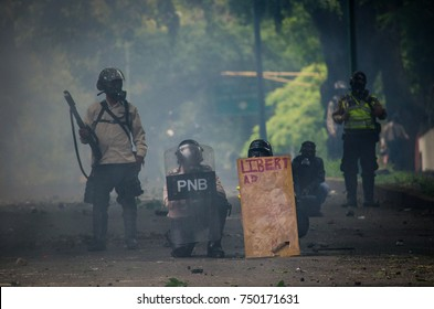 CARACAS, VENEZUELA - MAY 01, 2017: Protest in Caracas, Venezuela against the government of Nicolas Maduro. The national police uses a wooden shield that they stole from the Venezuelan resistance