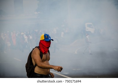 CARACAS, VENEZUELA - MAY 01, 2017: Protest in Caracas, Venezuela against the government of Nicolas Maduro. Demonstrator in a cloud of tear gas.