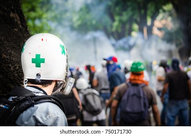 """CARACAS, VENEZUELA - MAY 01, 2017: Protest in Caracas, Venezuela against the government of Nicolas Maduro. First aid group, """"Green Cross"""" waits to attend all the injured in the protests."""