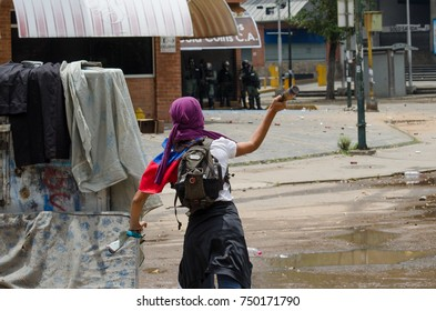 CARACAS, VENEZUELA - MAY 01, 2017: Protest in Caracas, Venezuela against the government of Nicolas Maduro. Demonstrator launches glass bottle towards the national guard.