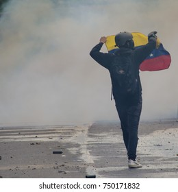 CARACAS, VENEZUELA - MAY 01, 2017: Protest in Caracas, Venezuela against the government of Nicolas Maduro. Demonstrator waves the flag of Venezuela in a cloud of tear gas.