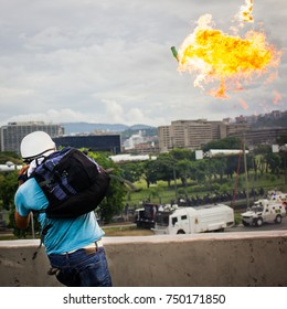 CARACAS, VENEZUELA - MAY 01, 2017: Protest in Caracas, Venezuela against the government of Nicolas Maduro. Demonstrator launches Molotov bomb to the national guard.