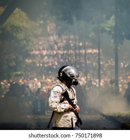 CARACAS, VENEZUELA - MAY 01, 2017: Protest in Caracas, Venezuela against the government of Nicolas Maduro. National police officer with his back to hundreds of Venezuelan demonstrators