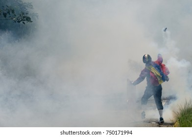CARACAS, VENEZUELA - MAY 01, 2017: Protest in Caracas, Venezuela against the government of Nicolas Maduro. Protester returns tear gas bomb to the national guard.