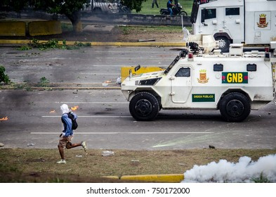 CARACAS, VENEZUELA - MAY 01, 2017: Protest in Caracas, Venezuela against the government of Nicolas Maduro. Protester flees from the repression of the national guard.