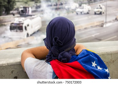 CARACAS, VENEZUELA - MAY 01, 2017: Protest in Caracas, Venezuela against the government of Nicolas Maduro. Protester observes and prepares to resist the attacks of the Bolivarian National Guard.
