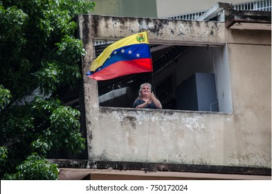 CARACAS, VENEZUELA - MAY 01, 2017: Protest in Caracas, Venezuela against the government of Nicolas Maduro. Older lady takes out her flag from her home in support of the protests.