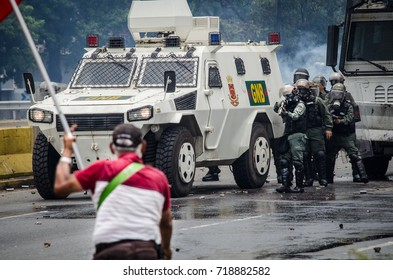 CARACAS, VENEZUELA - MAY 03, 2017: A deputy of the Venezuelan National Assembly stands in front of the National Guard with a flag and is aimed with a shotgun.