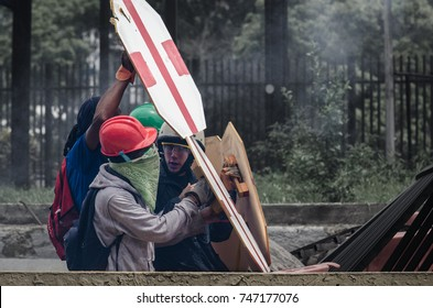 CARACAS, VENEZUELA - MAY 3, 2017: Protest in Caracas, Venezuela. Young protesters of the Venezuelan resistance, with wooden shields with which they defend themselves from tear gas and pellets.