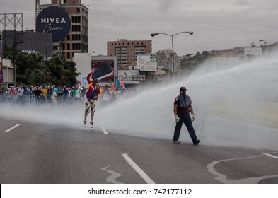 CARACAS, VENEZUELA - MAY 3, 2017: Protest in Caracas, Venezuela. Young protesters are repressed by the Bolivarian National Guard with jets of water with high pressure.