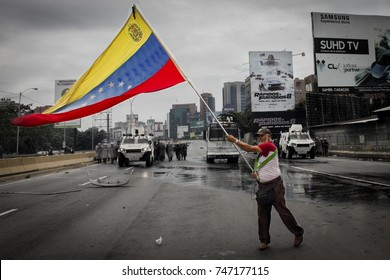 CARACAS, VENEZUELA - MAY 3, 2017: Protest in Caracas, Venezuela. Deputy of the National Assembly holds a Venezuelan flag when the protest is repressed by the Bolivarian National Guard with tear gas.