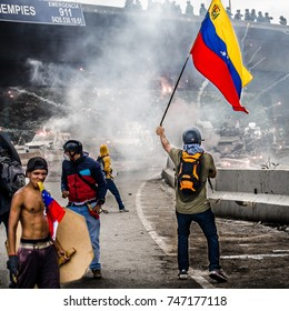 CARACAS, VENEZUELA - MAY 3, 2017: Protest in Caracas, Venezuela. You protester holds a Venezuelan flag when the protest is repressed by the Bolivarian National Guard with tear gas.