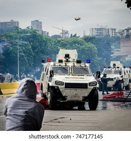 CARACAS, VENEZUELA - MAY 3, 2017: Protest in Caracas, Venezuela. Protester throws a stone against the tank of the Bolivarian National Guard.