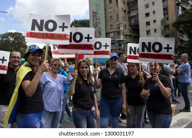 Caracas/Venezuela - January 30, 2019: Protesters hold banners that reads NO MORE DICTATORSHIP in a show of strength for Juan Guaido, the U.S. backed opposition leader declared himself interim presiden