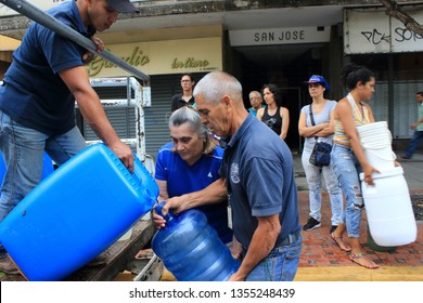 Caracas/Venezuela, March 2019: Families gathered up plastic bottles to fill them with hosepipes. Water shortages caused by a six-day power cut in Venezuelan cities hit the headlines earlier this month