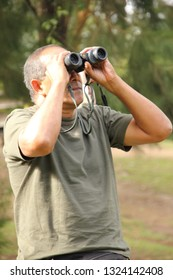 Caracas/Venezuela October 27, 2018: Naturalist in the outdoors learning how to identify bird species and birdwatching basis in the outdoors with binoculars El Avila National Park