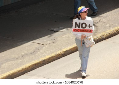 Caracas/Venezuela-02/16/2017: Protesters of the government of Nicolas Maduro and former president Hugo Chavez during a rally in Caracas with banners that reads NO MORE DICTATORSHIP