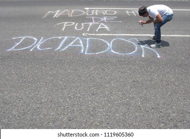 Caracas/Venezuela-04/26/2017: Venezuelan protester against Nicolas Maduro government painting a graffiti during the second 2017 street protest movement called El Plantazo sit-in of civil insurrection