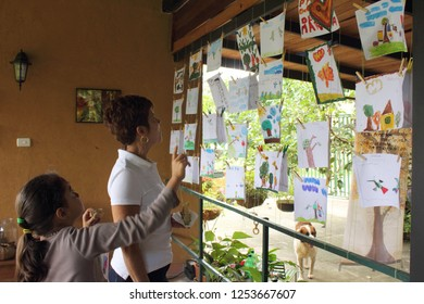 Caracas/Venezuela-April 22, 2018: a teacher and a kid looking at drawings by scholar kids on the earth day showcasing nature