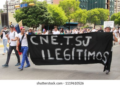 Caracas/Venezuela-April 30th, 2017: Opposition protesters with a banner that reads CNE Consejo Nacional Electoral and TSJ Tribunal Supremo de Justicia illegitimate. May 2017