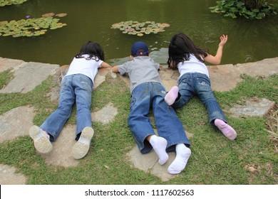 Caracas/Venezuela-March 21, 2017: Kids exploring the water in a pond in a garden Topotepuy