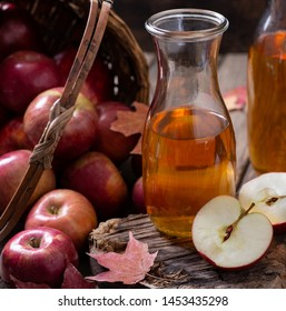 Carafe of cider and apple sliced in half  on rustic wood with a basket of red apples spilled in background