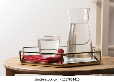 Carafe and glass with water on table indoors. Space for text