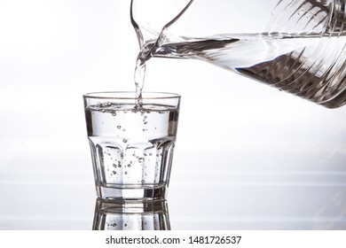 From the carafe pours pure drinking water into a glass cup. A stream of water and transparent droplets on the wall of the glass.