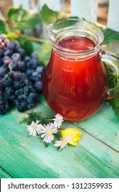Carafe of red wine with a bunch of grapes and flowers