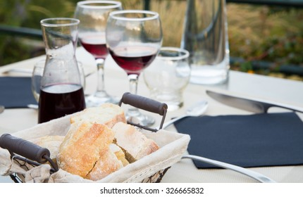 Carafe of red wine with two glasses on the table with dinner dishes.