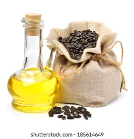 Carafe with vegetable oil and bag with sunflower seeds isolated on white