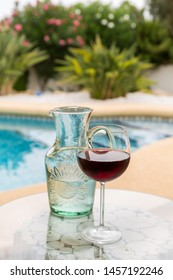 Carafe of water and glass wine with swimming pool in background
