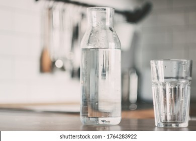 A carafe of water on the kitchen wooden table. Bottle of water. the concept of a healthy lifestyle