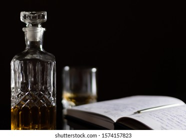 A carafe of whiskey stands next to a business diary and a glass of whiskey on a black glass table on a black background