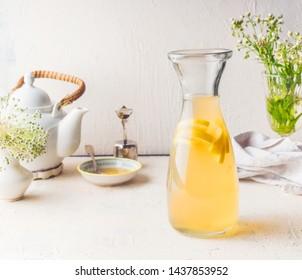 Carafe with white tea citrus lemonade drink on white kitchen table. Summer beverage concept