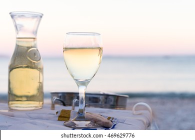 The carafe of white wine and a glass of wine on the beach, sunset, dinner by the sea, holiday, romance. Holidays in Greek wine in Greece. Tavern on the sea shore