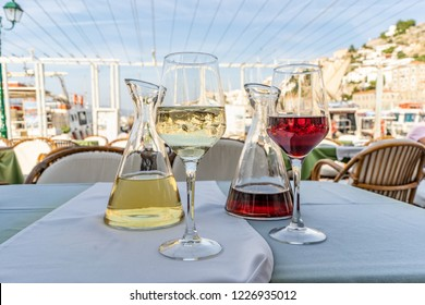 A carafe of white wine with ice and a carafe of red wine, with glasses, ready to drink at an outdoor cafe overlooking the harbor on the enchanting Greek Island of Hydra.